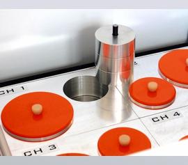"""Isothermes 4-Kanal Mörtel- und Betonkalorimeter Calmetrix I-Cal 4000 HPC mit geöffnetem Deckel – Detailansicht eines der vier Messplätze in Zwillingsbauweise (Mess- und Referenzseite) und der """"Referenzprobe"""" mit den drei variablen Metallscheiben"""