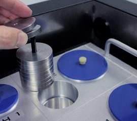 """Isothermes Vier-Kanal Biokalorimeter Calmetrix Biocal 4000 mit geöffnetem Deckel – Detailansicht einer """"Referenzprobe"""" mit den separaten Metallscheiben, aufgesteckt auf einem Halter"""