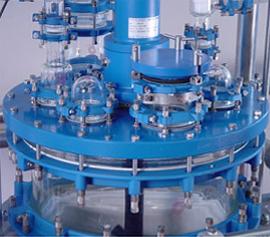 Glasreaktor mit solider emaillierter Deckelplatte und explosionsgeschützter Rührwellendichtung und großem Handloch.