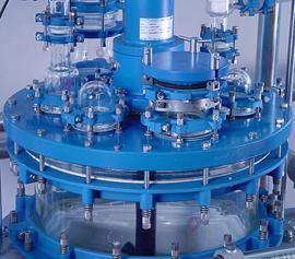 Reaktor mit solider emaillierter Deckelplatte, explosionsgeschützter Rührwellendichtung und großem Handloch.